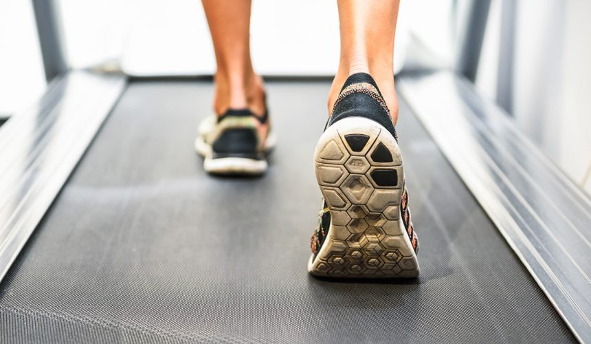 Male muscular feet in sneakers running on the treadmill at the gym. Concept for fitness, exercising and healthy lifestyle.
