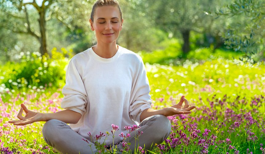 Beautiful calm girl with closed eyes meditating in the fresh blooming garden, unity with nature, zen balance, happy healthy lifestyle